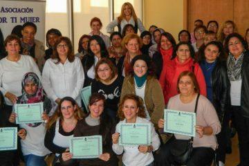 Un grupo de mueres exhiben sus diplomas tras haber realiza- do un curso de empoderamiento en la Asociación Por ti mujer.